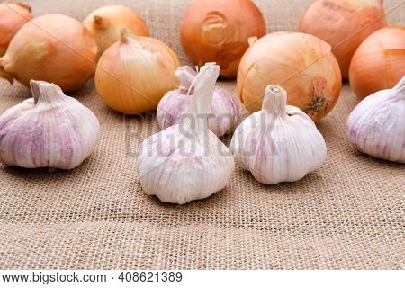 Bulbs Of Garlic And Onions Lie On A Burlap Cloth.