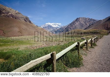 Wooden Fence Along Hiking Trail In Aconcagua National Park With View To Snow Caped Highest Mountain