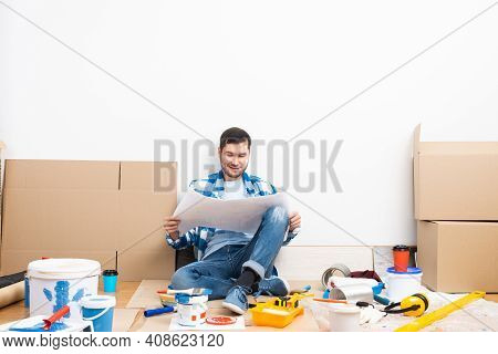 Happy Guy Sitting On Floor With Paper Blueprint. Home Remodeling After Moving. Construction Tools An