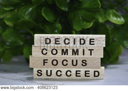 Inspirational Words Of Decide Commit Focus Succeed On Wooden Blocks With Green Background