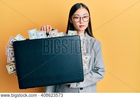 Young chinese woman holding briefcase full of dollars relaxed with serious expression on face. simple and natural looking at the camera.