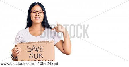 Young beautiful asian girl holding save our democracy protest banner pointing finger to one self smiling happy and proud