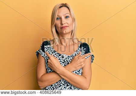 Middle age caucasian woman pointing up with fingers to different directions relaxed with serious expression on face. simple and natural looking at the camera.