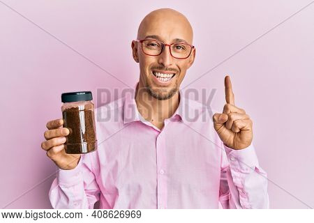 Bald man with beard holding soluble coffee smiling with an idea or question pointing finger with happy face, number one