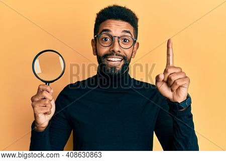 Handsome hispanic man with beard holding magnifying glass smiling with an idea or question pointing finger with happy face, number one