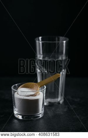 Collagen Powder In Bowl, Glass Of Water And Measure Spoon On Black Background. Extra Protein Intake.