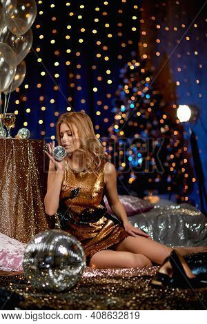 Sexy Curly Blonde Woman In A Gold Sequins Party Dress Is Holding Mirror Ball In Luxury Interior Desi