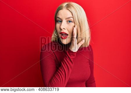 Young blonde woman wearing casual clothes hand on mouth telling secret rumor, whispering malicious talk conversation