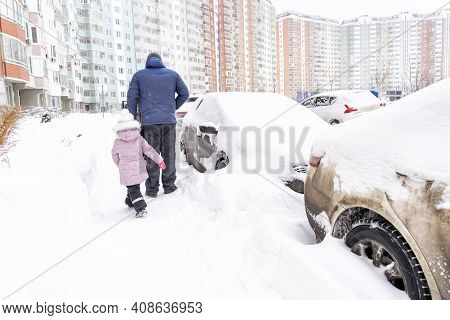 Cars Are Covered With Snow Near A Multi-storey Residential Building. Passersby Look At The Problem