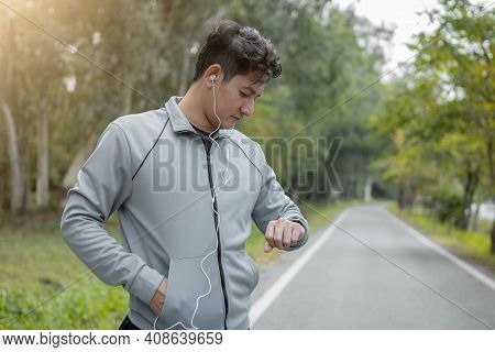 Male Runner Using Smart Watch To Monitor Performance. Sport Man Is Setting Up His Smart Watch Before