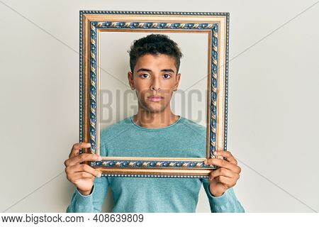 Young handsome african american man holding blank empty banner relaxed with serious expression on face. simple and natural looking at the camera.
