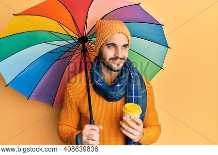 Young hispanic man holding colorful umbrella drinking take away coffee smiling looking to the side and staring away thinking.