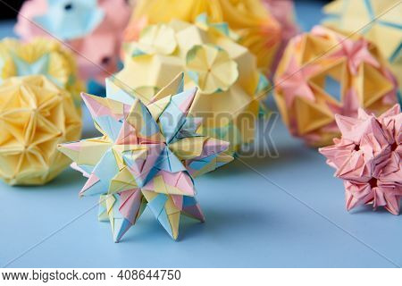 Pink Handmade Modular origami Ball Or Kusudama Isolated On Blue Background. Visual Art, Geometry, Ar