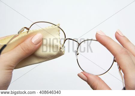 The Girl Manually Cleans The Lenses Of Her Reading Glasses On A Light Background. A Soft Cloth For W