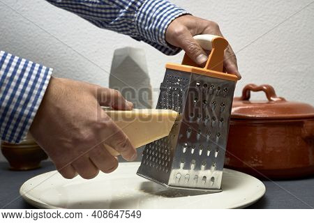 Grating Cheese With A Metal Grater And A Piece Of Italian Cheese