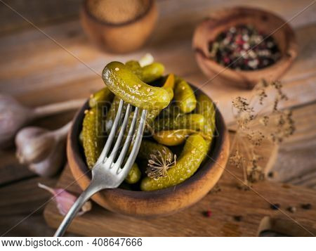 Gherkins, Pickled Cucumber On A Fork, Bowl Of Marinated Vegetables On Rustic Wooden Background. Clea