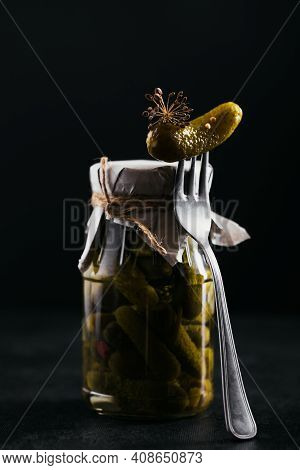 Homemade Canning. Marinated Cucumbers Gherkins With Dill And Garlic In A Glass Jar On Black Backgrou