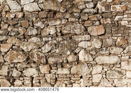 Old Stone Wall, Painted In A Faded White Color And Built With Stones And Mud