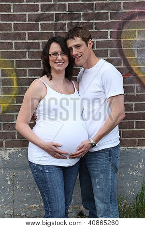 Maternity photos of a couple with brink wall as a background - 8 months pregnant poster