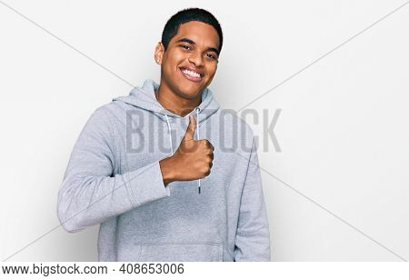 Young handsome hispanic man wearing casual sweatshirt doing happy thumbs up gesture with hand. approving expression looking at the camera showing success.