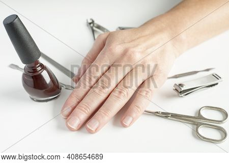 Manicure Tools And Female Hand On White Background. Making Self-manicure At Home Concept.