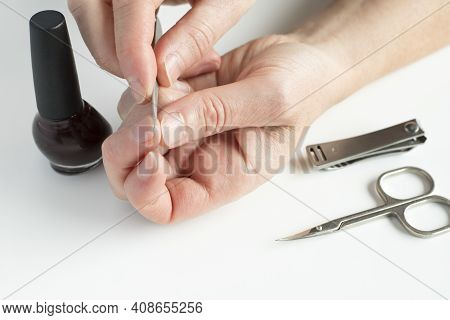 Woman Doing Manicure To Herself. Female Hands, Holding Nail File, With Nail Polish, Scissors And Nai