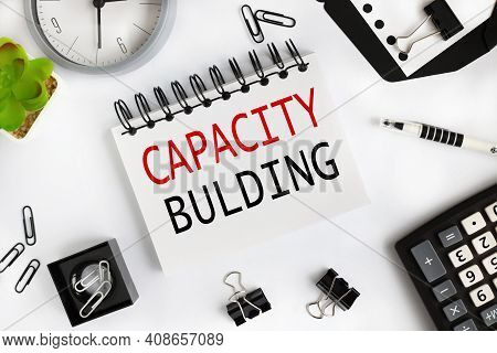 Capacity Building. Text On White Notepad Paper On Light Background Near Calculator, Plant, Table Clo