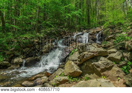 Small Waterfall With Water Splashing And Tumbling Over The Rocks And Boulders In The Forest On A Bri