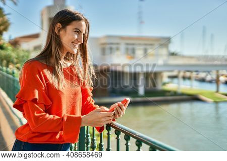 Young hispanic woman smiling happy using smartphone leaning on the balustrade.