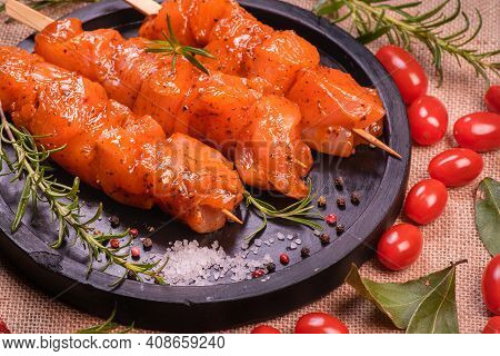 Chicken Pieces Of Kebabs Marinated In A Red Marinade With Spices On A Dark Culinary Board, On A Back