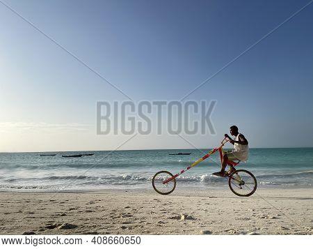 Zanzibar, - Tanzania, January 10, 2021:  Young Black Man Smiling And Riding A Self Maiden Funny Brig