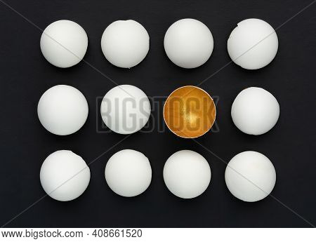 White And Gold Eggshell On A Black Background. The Concept Of Difference Among Equals. Talent Awaken