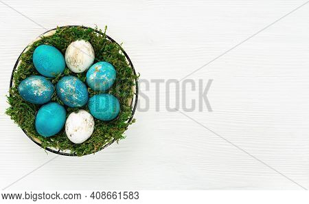 Easter Basket With Turquoise And Gold Eggs On A White Wooden Background Top View. Easter Banner With