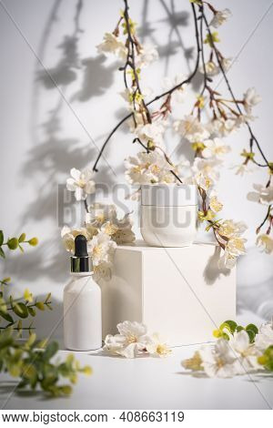 Cosmetic Cream And Serum Or Essential Oil Bottle On White Background With Flowers And Leaves. Bright