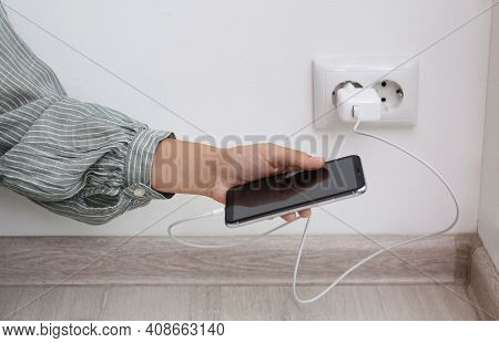 Woman Holding Mobile Phone With Connected Charger Near White Brick Wall Indoors, Closeup