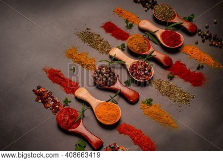 Various Kinds Of Spices On Wooden Spoons Background. Free Space For Text Inside.