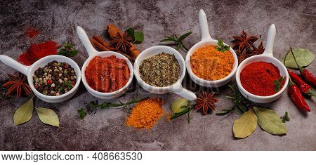 Various Kinds Of Spices On Spoons Background.