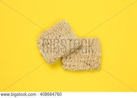Instant Noodles, Ramen, Dried Noodle Blocks On A Yellow Background. Unhealthy Food Concept. Uncooked