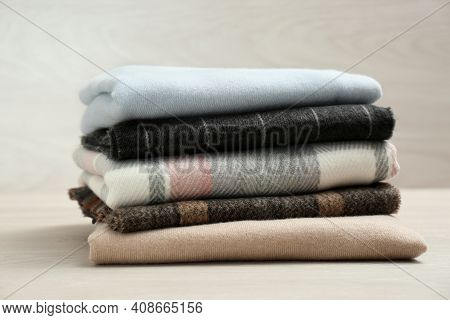 Stack Of Cashmere Clothes On Wooden Table