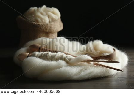Soft White Wool With Spindles On Wooden Table