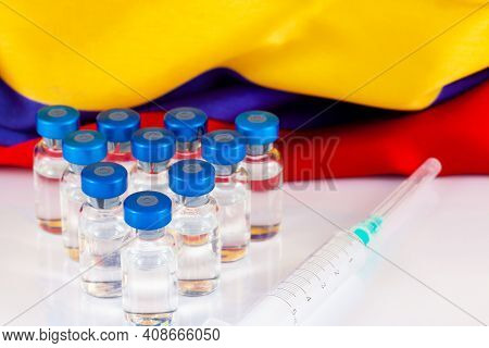 Vaccine Vials And Colombian Flag. Vaccination Concept.