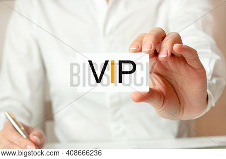 A Woman In A White Shirt Holds A Piece Of Paper With The Text: Vip. Business Concept For Companies.