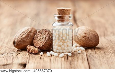 Nutmeg with homeopathic globules nux moschata on wooden background