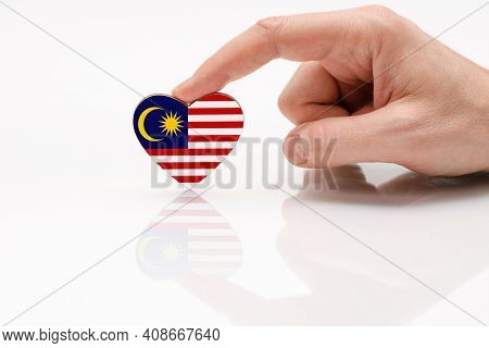Love And Respect Malaysia. A Man's Hand Holds A Heart In The Shape Of The Malaysia Flag On A White G