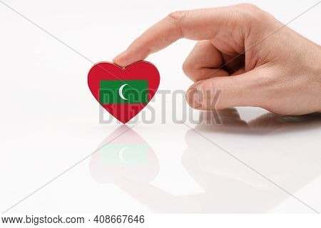 Love And Respect Maldives. A Man's Hand Holds A Heart In The Shape Of The Maldives Flag On A White G