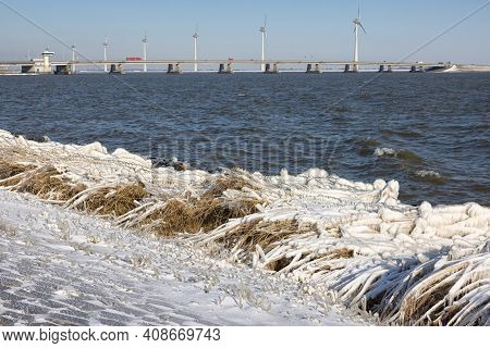 Dutch Breakwater With Basalt Rocks And Reed Border Covered With Snow And Ice In Wintertime