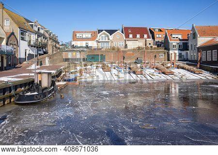 Urk, The Netherlands - Februari 13, 2021: Frozen Harbor Of Urk With Shipyard And Old Tugboat