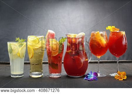 Horizontal View Of Colorful Lemonades With Ice Cubes, Mint Sprig, Lemon, Orange, Watermelon Slices.
