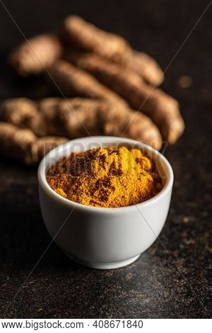 Indian turmeric powder and root. Turmeric spice. Ground turmeric in bowl on black table.