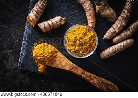 Indian turmeric powder and root. Turmeric spice. Ground turmeric in wooden spoon. Top view.